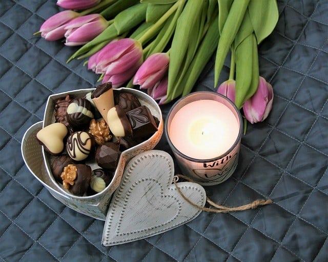bukiet kwiatów świeca i czekoladki